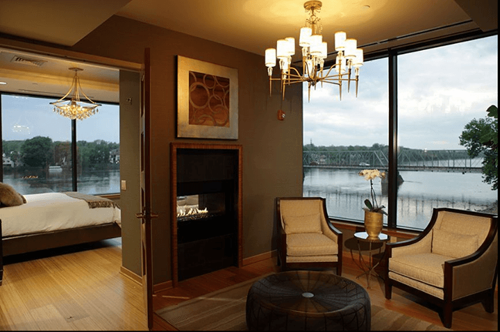hotel suite with hardwood floors and a fireplace against a backdrop of the river
