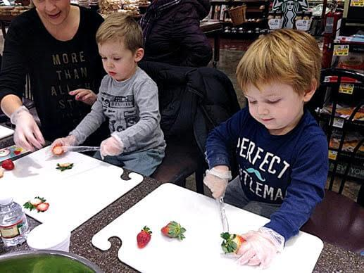 toddlers cutting the stems off of strawberries