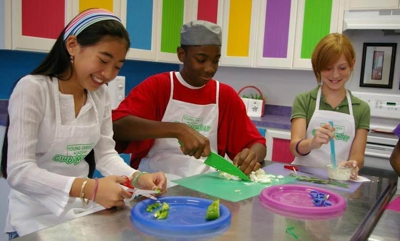 children preparing food around a table for cooking class