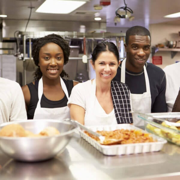 Portrait Of Kitchen Staff In Homeless Shelter Volunteering for Thanksgiving