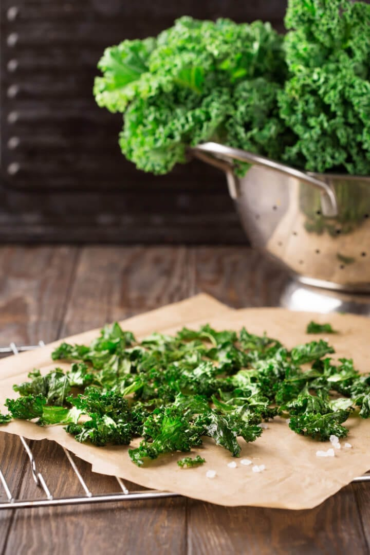 Homemade kale chips on rustic wooden background, selective focus