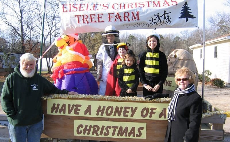 group around sign reading have a honey of a christmas