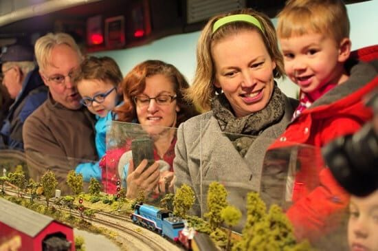 family looking at model railroad