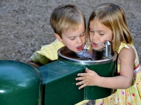 two children drinking from water fountain