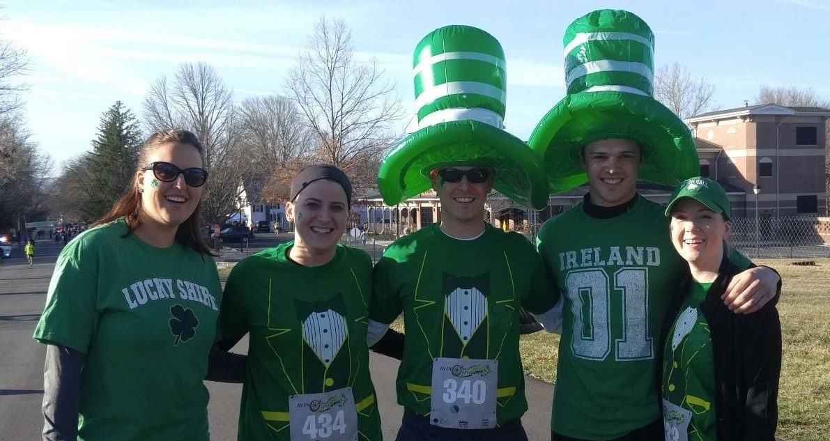 five runners in green shirts and hats at Family-friendly event