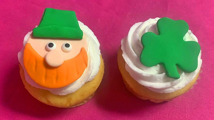 two cupcakes decorated with a leprechaun and a shamrock