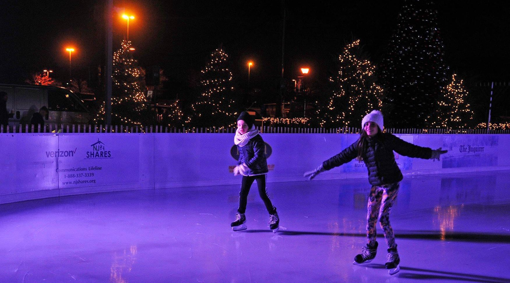 children ice skating with christmas trees in background